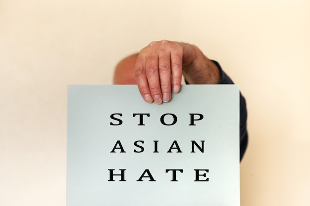 Stop asian hate concept. men hand holding card paper sheet with word stop asian hate for poster of campaign