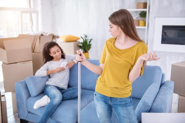 Перестань лениться. раздраженная молодая девушка моет пол в новой квартире и ругает свою соседку по комнате, пока она не помогает ей, а пишет смс