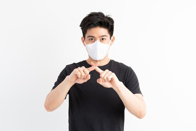 ストップシビッド-19、フェイスマスクを身に着けているアジア人男性は、コロナウイルスの発生を止めるためのストップハンドジェスチャーを示しています