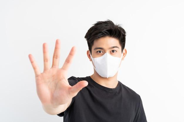 Stop civid-19, uomo asiatico che indossa la maschera per il viso mostra il gesto delle mani per fermare l'epidemia di virus corona
