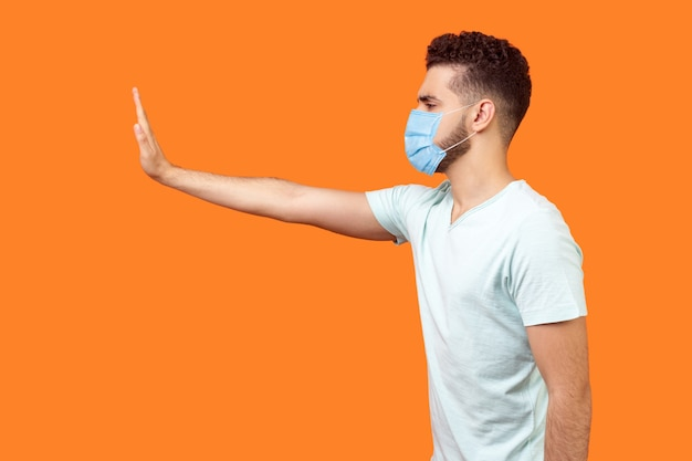 Stop, don't come any closer. side view of serious bossy man with surgical medical mask standing holding out hand to left, prohibition gesture, saying no. studio shot isolated on orange background