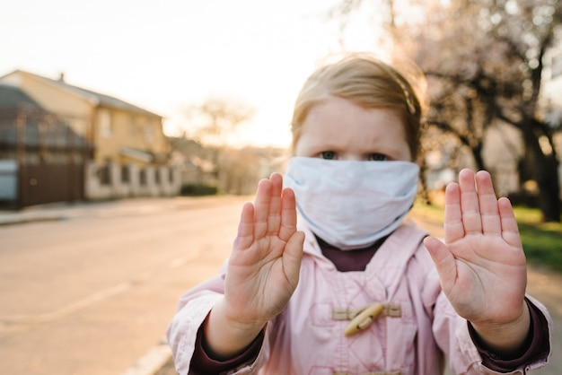 Stop the coronavirus and virus epidemic diseases. healthy child in medical protective mask showing gesture stop. health protection and prevention during flu and infectious outbreak