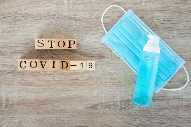 木製のテーブルの生地のフェイスマスクと消毒剤アルコールゲルボトルの平面図です。 「stop covid-19」というテキスト付き予防コロナウイルス(covid-19)病の場合。