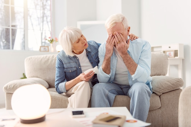 Stop crying. loving elderly woman sitting on the sofa next to her crying husband and hugging him, trying to console, while he crying