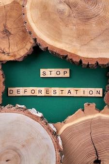 森林破壊をやめましょう。緑の背景に木製のスライス。