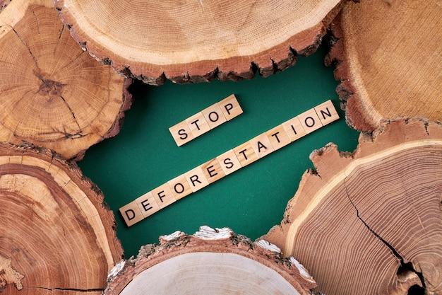 森林破壊の木製の立方体を止めてください。緑の背景に垂直ショット木製スライス。