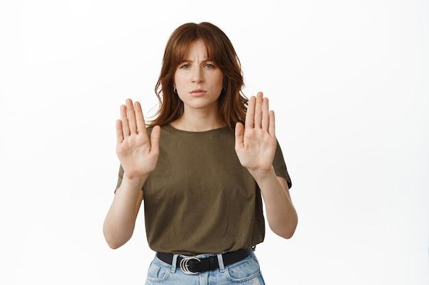 やめて、近づかないで。真面目な若い女性は手を伸ばし、ブロック拒否のジェスチャーを示し、行動に不満を抱き、距離を保つように言い、後ろに留まり、白の上に立つ