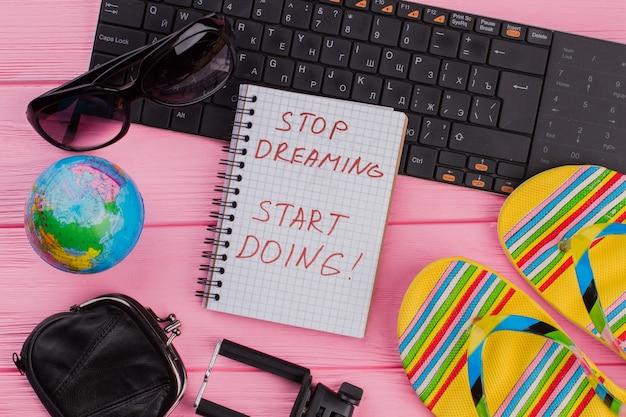 ピンクのテーブルトップの背景に女性の旅行者アクセサリーメガネ財布とビーチサンダルでノートブックでやり始めることを夢見るのをやめます。地球儀と黒のキーボード。