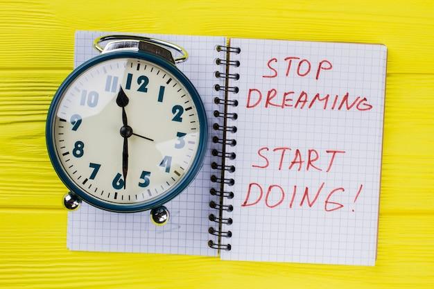 Перестань мечтать, начни делать. круглый будильник и блокнот с цитатой мотивации.