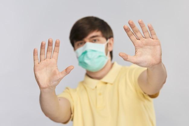 노란색 셔츠를 입은 젊은 잘 생긴 남자의 손바닥으로 제스처를 중지하고 covid-19 코로나 바이러스 동안 사회적 거리를 두십시오.