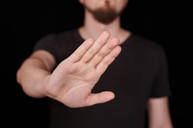 一時停止の標識。黒のtシャツを着た男が歌うのをやめます。いいえ、コンセプトを拒否します。