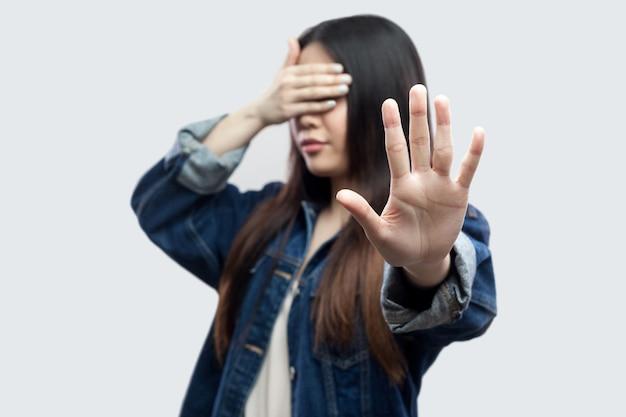 やめて、これは見たくない。目を閉じて立って停止ジェスチャーを示すカジュアルな青いデニムジャケットで怖がっているブルネットの若い女性の肖像画。明るい灰色の背景に分離された屋内スタジオショット
