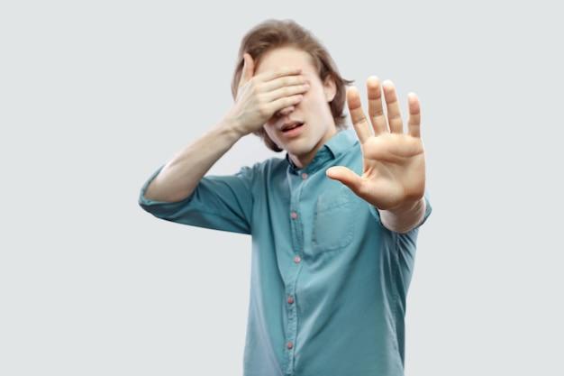 やめて、これは見えない。ブロックの手で立って目を覆っている青いカジュアルなシャツを着たハンサムな長い髪の金髪の若い男の肖像画。明るい灰色の背景に分離された屋内スタジオショット。