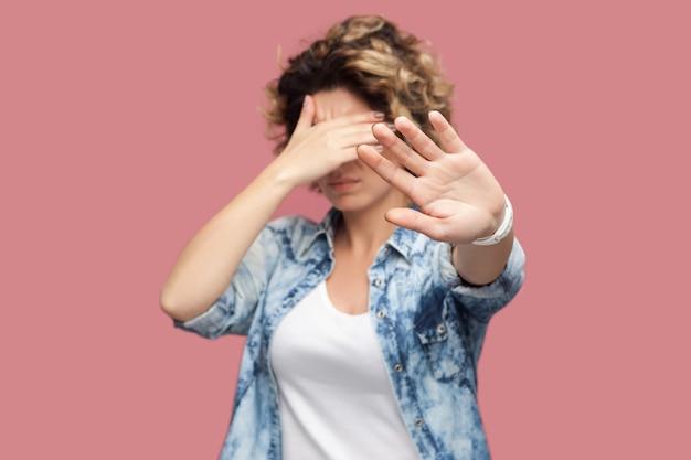やめて、これは見たくない。彼女の目を覆い、一時停止の標識を示している巻き毛の立っている混乱または怖がっている若い女性の肖像画。ピンクの背景に分離された屋内スタジオショット。