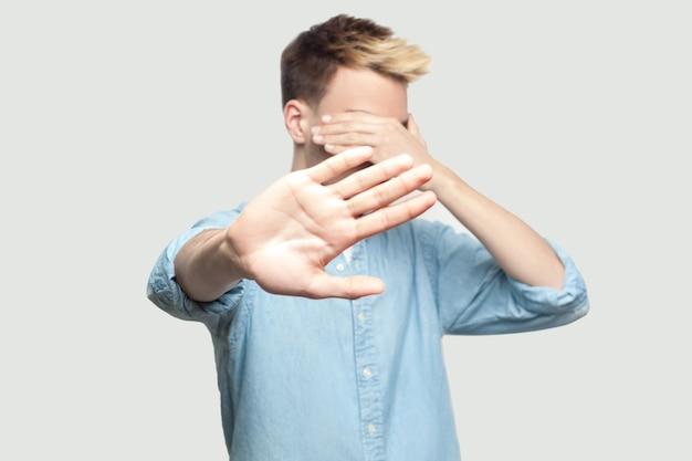 やめて、これは見たくない。水色のシャツを着て立って、顔を覆い、ストップハンドジェスチャーを示している怖いハンサムな若い男の肖像画。灰色の背景のコピースペースで撮影された屋内スタジオ