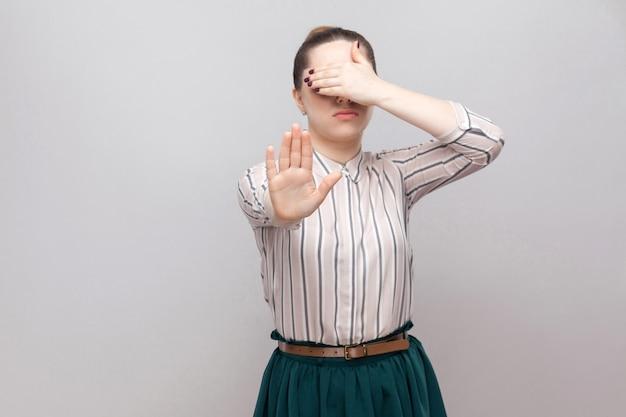 やめて、見たくない。ストライプのシャツと緑のスカートの立っている美しい若い女性の肖像画、停止ジェスチャーと彼女の目を覆った。灰色の背景に分離された屋内スタジオショット。