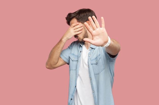 やめて、これは見たくない。青いカジュアルなスタイルのシャツを着て立って、目を覆い、ストップハンドサインジェスチャーを示しているひげを生やした若い男の肖像画。ピンクの背景に分離された屋内スタジオショット