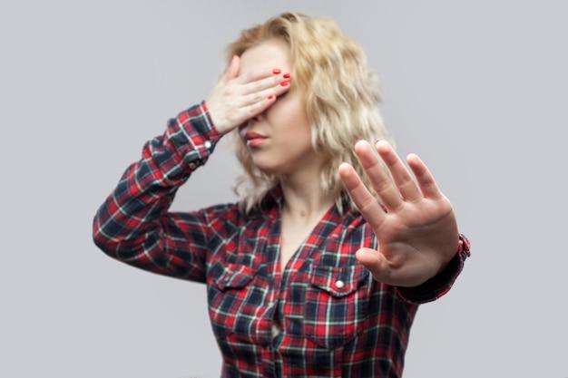 やめて、これは見たくない。停止ジェスチャーで立って目を覆っているカジュアルな赤い市松模様のシャツを着た美しい金髪の若い女性の肖像画。スタジオショット、灰色の背景に分離。