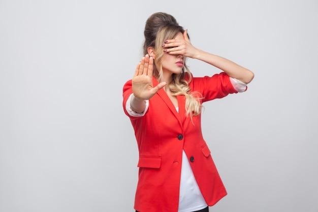やめて、これは見たくない。赤い派手なブレザーで髪型とメイクの美しいビジネス女性の肖像画、停止手で彼女の目を覆って立っています。スタジオショット、灰色の背景に分離。