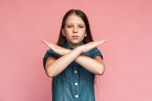 그만해, 내가 경고하고 있어. 화난 결정된 어린 소녀의 초상화가 손을 교차하고 공격적으로 카메라를 쳐다보며 정지 제스처를 보여주고 금지된 방법을 보여줍니다. 실내 스튜디오 촬영 분홍색 배경