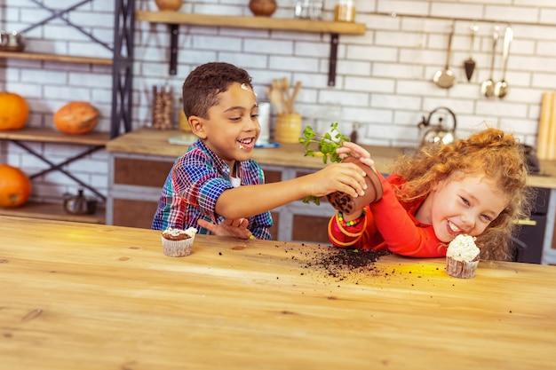 멈춰. 식물을 가지고 노는 동안 긍정을 표현하는 기뻐하는 아이들