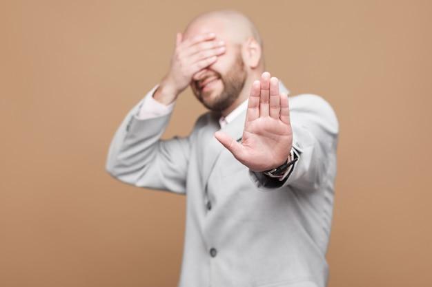 やめて、見たくない。停止ジェスチャーで立っている古典的なライトグレーのスーツを着た混乱した中年のハゲひげを生やしたビジネスマンの肖像画は、彼の目を覆った。スタジオは茶色の背景で撮影しました。