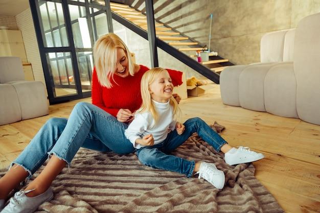Прекрати. радостная молодая женщина, сохраняя улыбку на лице, щекоча свою дочь