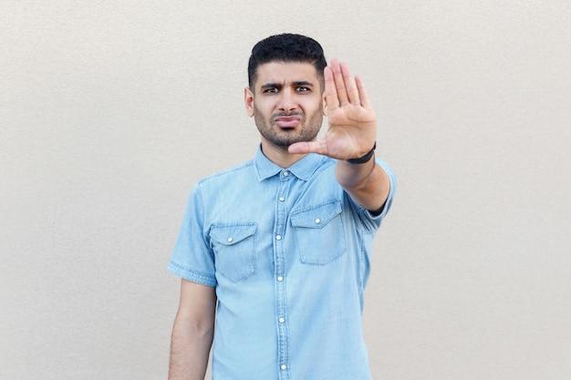 그만 해요. 파란색 셔츠를 입은 화난 진지한 잘생긴 청년의 초상화는 손짓으로 서서 카메라를 바라보고 있습니다. 밝은 베이지색 벽 배경에 격리된 실내 스튜디오.