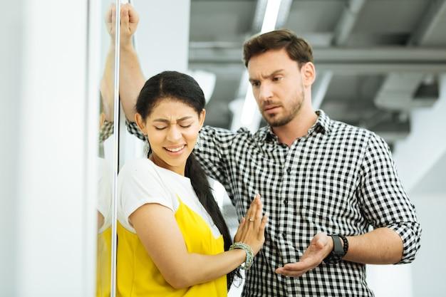 멈춰. 그녀의 손을 들고 그녀의 동료가 낭만적 인 데이트를 요구하는 것을 방지하는 젊은 심각한 소녀