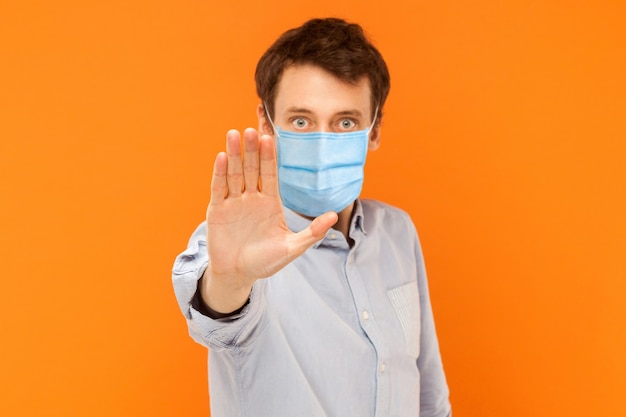 Stop! keep your distance. portrait of angry or aggressive young worker man with surgical medical mask standing with stop hand and looking at camera. indoor studio shot isolated on orange background.