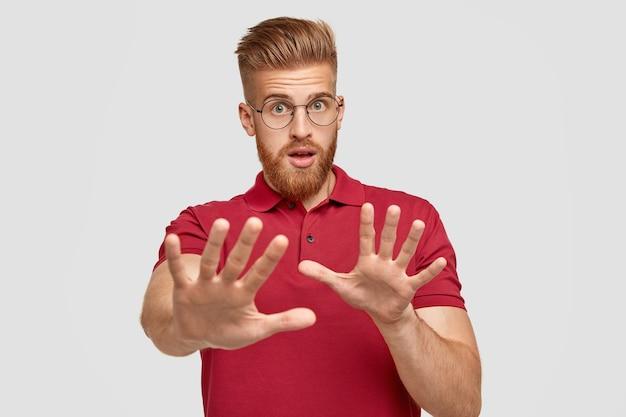 Fermati, lasciami in pace. uomo infelice intenso con barba e capelli voluminosi, mostra abbastanza o ferma il gesto,