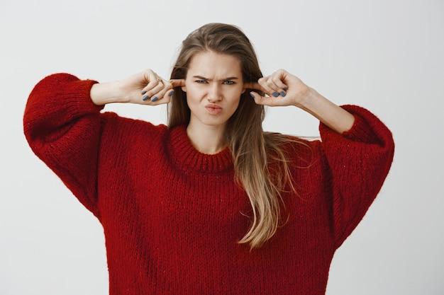 Smetti di fare rumori inquietanti. lo studio ha sparato alla donna attraente infastidita dispiaciuta in maglione sciolto alla moda, facendo tappi per le orecchie con gli indici, coprendo le orecchie e accigliato, odiando sentire il rumore fastidioso