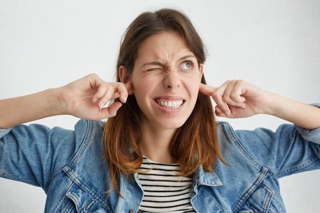 この迷惑な音を出すのをやめてください!不幸な顔の若い女性が苦しそうな顔をして、耳を指で差し込み、大きな音でイライラした
