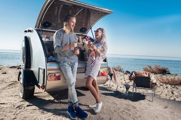 Остановка возле реки. современная пара чувствует себя незабываемой во время путешествия со своим мобильным домом, останавливающимся у реки