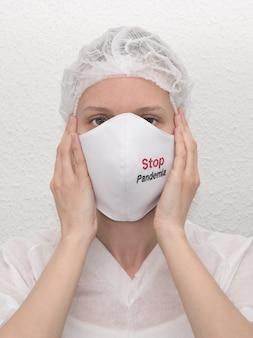 伝染性のウイルスを避けるために、stop pandemiaのサインが入った医療用マスクを着用している女性。