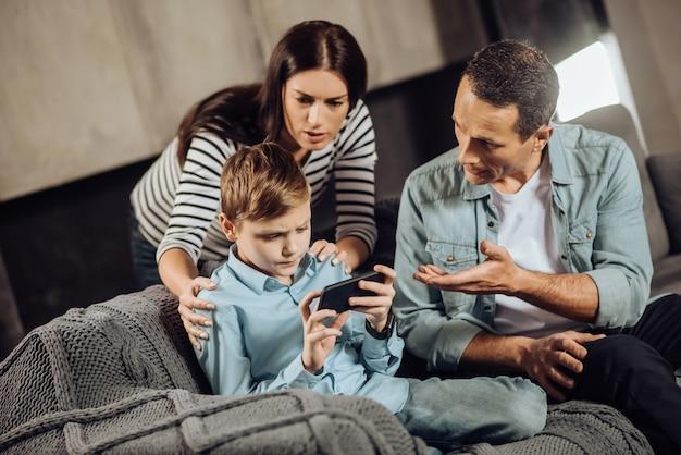 Хватит играть. любящие молодые родители стоят рядом со своим сыном-подростком и убеждают его положить трубку, в то время как мальчик отказывается, будучи упрямым.
