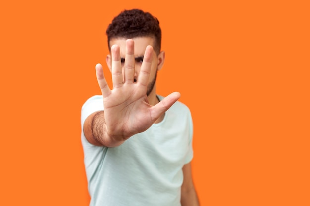 Stop. portrait of bossy brunette man in white t-shirt standing with outstretched hand hiding his face and showing prohibition gesture, saying no. indoor studio shot isolated on orange background