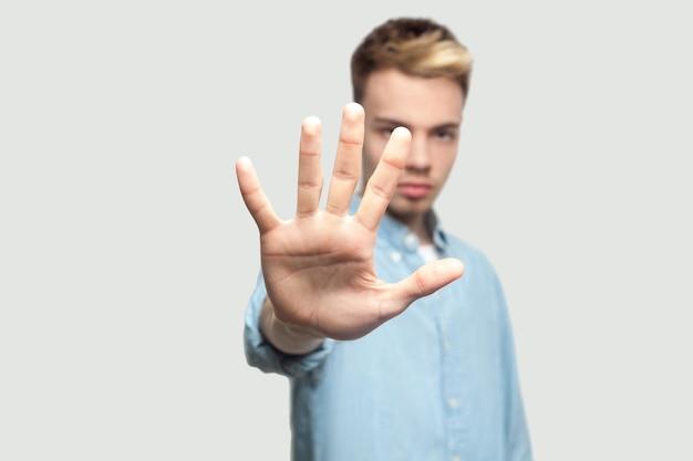 やめる。立って、怒りの顔でカメラを見て、停止手を示している水色のシャツを着た真面目なハンサムな若い男の肖像画。灰色の背景のコピースペースで撮影された屋内スタジオ。