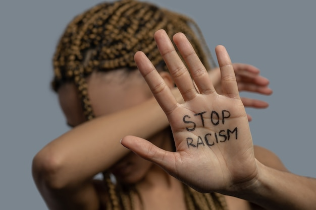 Stop racism. young african american woman showing palm with stop racism lettering, covering her face with elbow