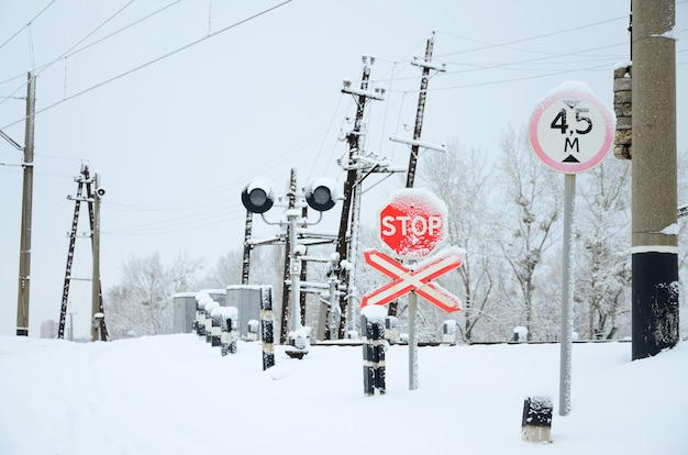 Стоп. красный дорожный знак расположен на автомагистрали, пересекающей железнодорожную линию в зимний сезон