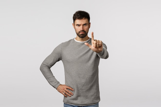 Stop right here. enough. serious-looking determined and confident bearded male friend warn partner, extend index finger and shaking it in restriction, forbid, prohibit action, stand