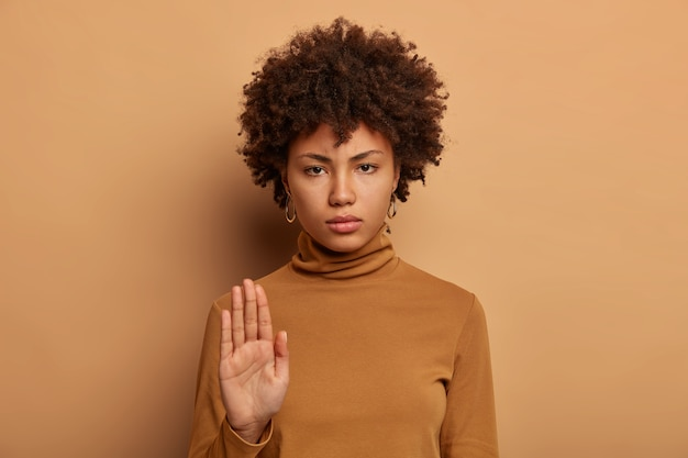 Stop right here. serious dark skinned woman stands with outstretched hand, makes prohibition gesture, forbids something, smirks face