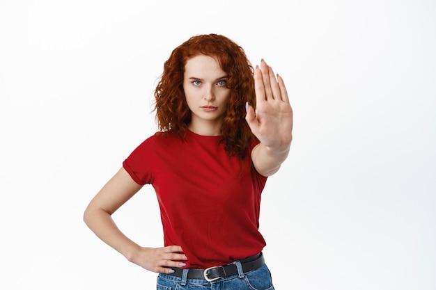 今すぐ停止します。真面目で断固とした赤毛の女性が手を伸ばしてブロックジェスチャーを見せ、ノーと言い、何か悪いことを拒否し、白い壁に立っている