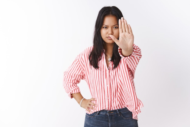 Stop right there. cute young asian female student says no to cosmetics tests on animals pulling palm in enough and no gesture frowning standing in powerful confident pose serious to prevent it