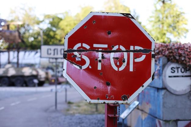 적대 행위 현장에서 도로 표지판을 중지하십시오. 금속의 총알 구멍.