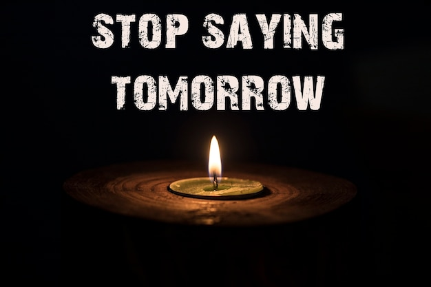 Stop saying tomorrow - white candle with dark background - in a wooden candlestick.