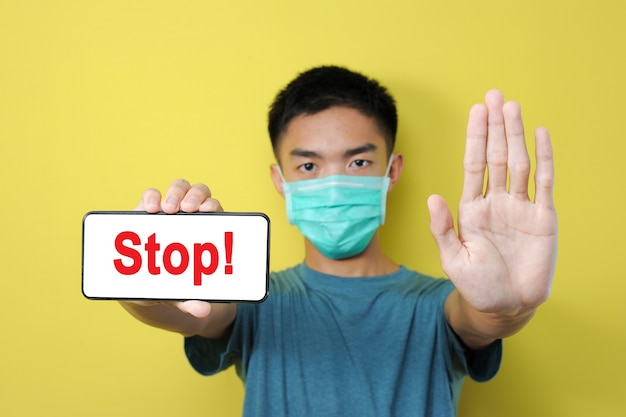 Stop share incorrect news about pandemic coronavirus, young asian man doing stop gesture to share hoax of coronavirus, isolated on yellow