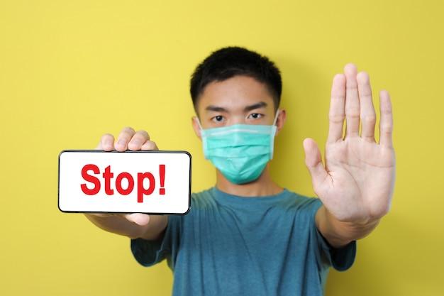 パンデミックコロナウイルスについての誤ったニュースを共有するのをやめなさい、コロナウイルスのデマを共有するために停止ジェスチャーをしている若いアジア人、黄色で隔離