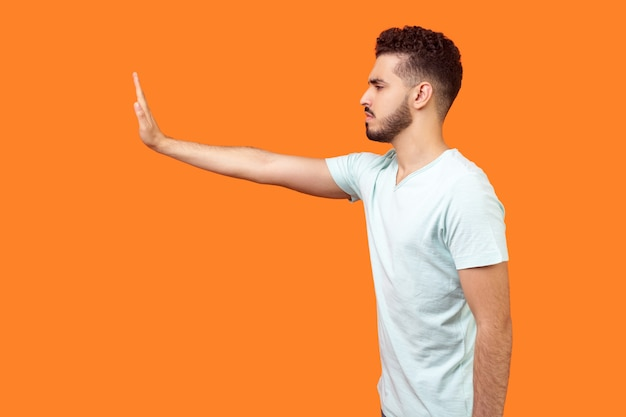Stop. side view of serious bossy brunette man in t-shirt standing holding out hand to left, prohibition gesture, saying no, empty copy space on left for text. studio shot isolated on orange background