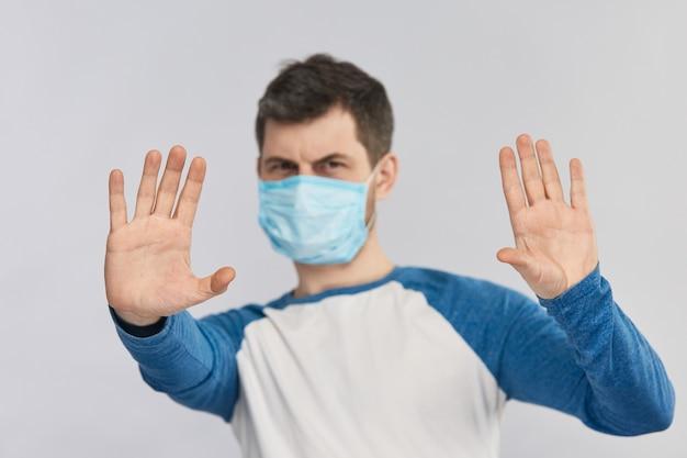 Covid-19 동안 보호 마스크를 착용 한 남자와 정지 신호 및 사회적 거리두기